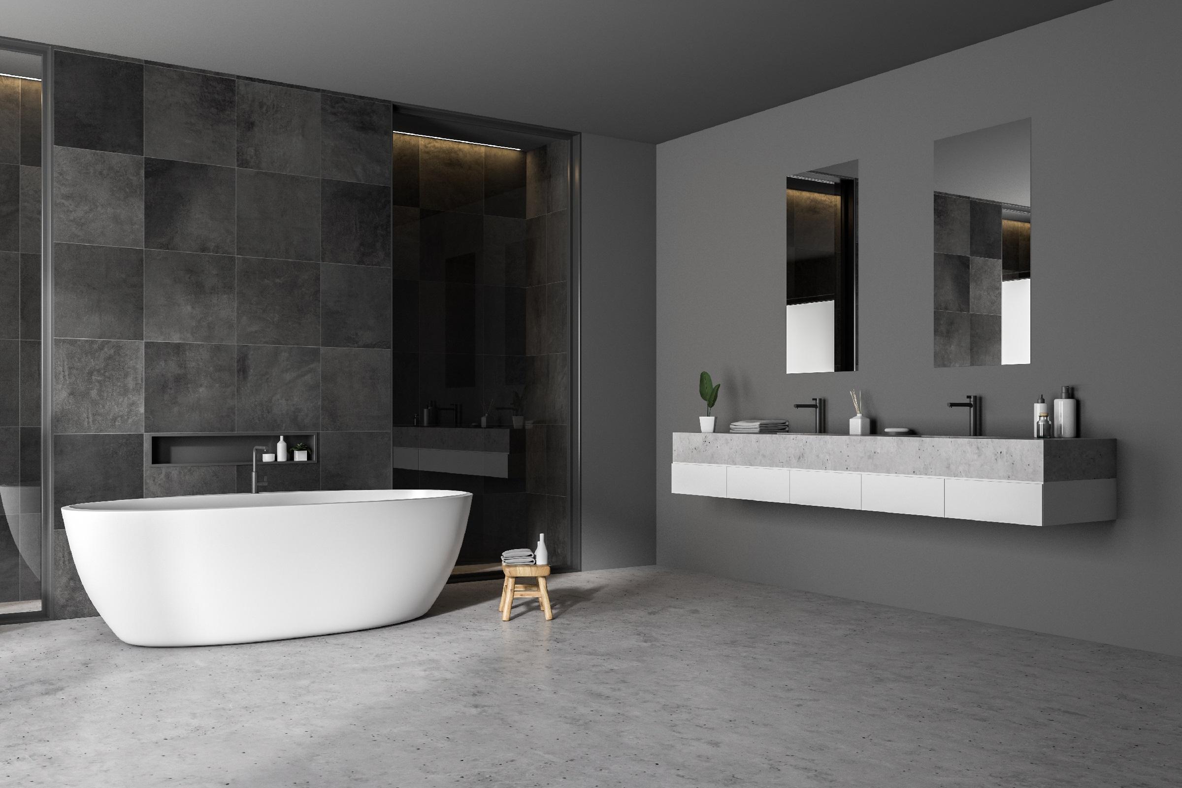 Modern bathroom corner with black tile walls, concrete floor, white bathtub and double sink. 3d rendering
