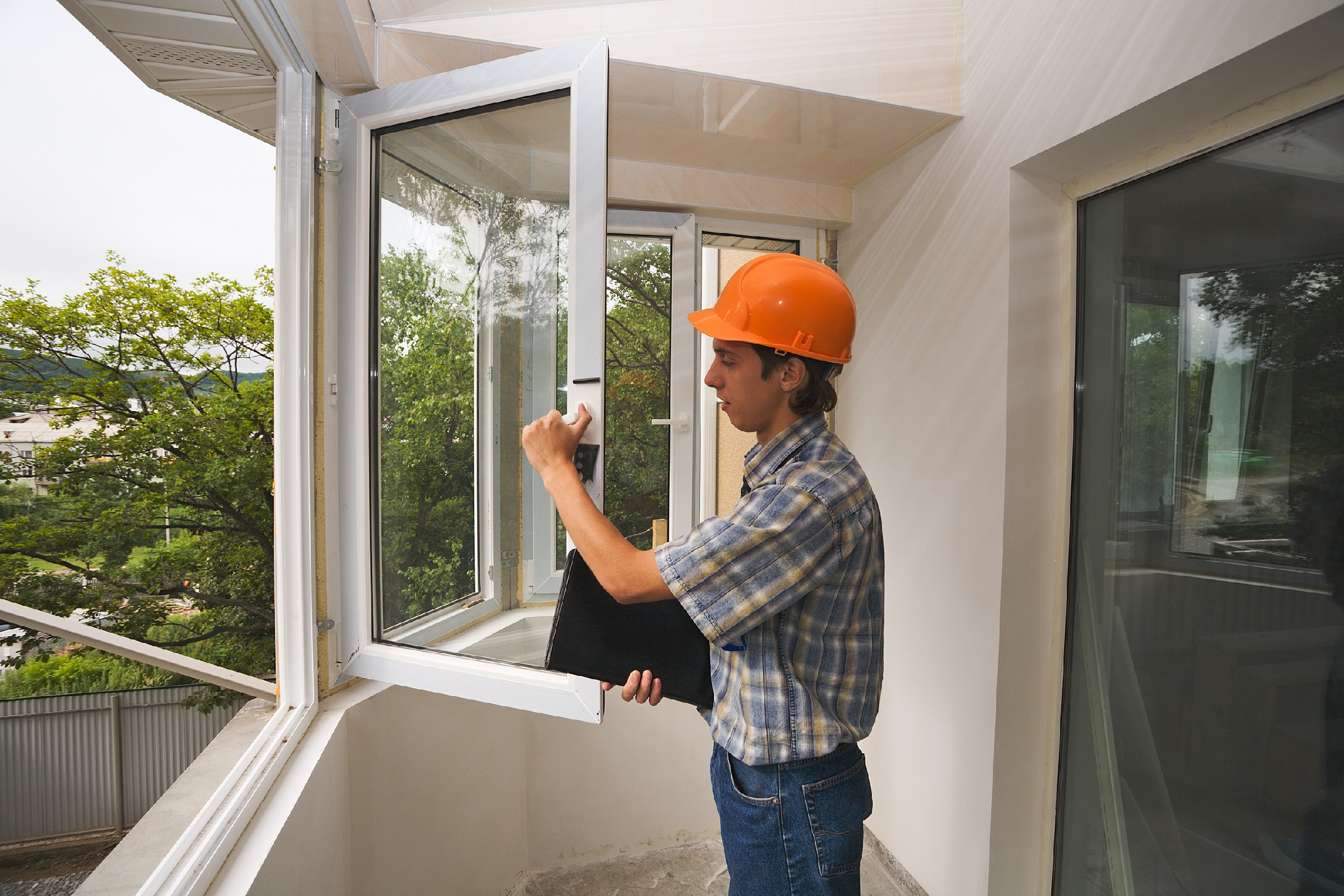 The building inspector checks quality of installation of new windows.